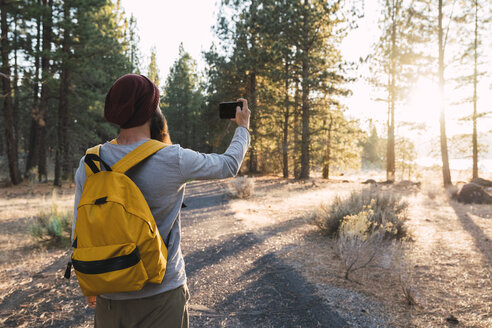 USA, North California, young man taking a selfie in a forest near Lassen Volcanic National Park - KKAF02976