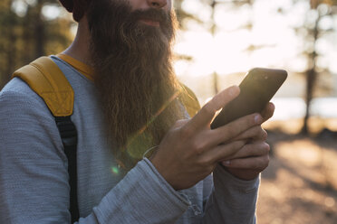 Close-up of bearded man using cell phone on a hiking trip in a forest - KKAF02982