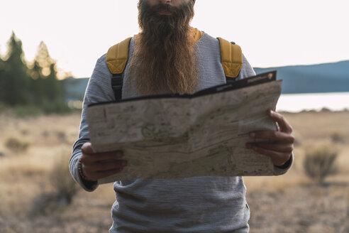 USA, North California, close-up of bearded man reading map on a hiking trip near Lassen Volcanic National Park - KKAF02988