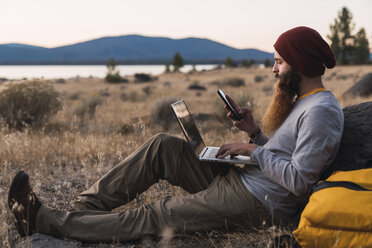 USA, North California, bearded young man using cell phone and laptop near Lassen Volcanic National Park - KKAF02991