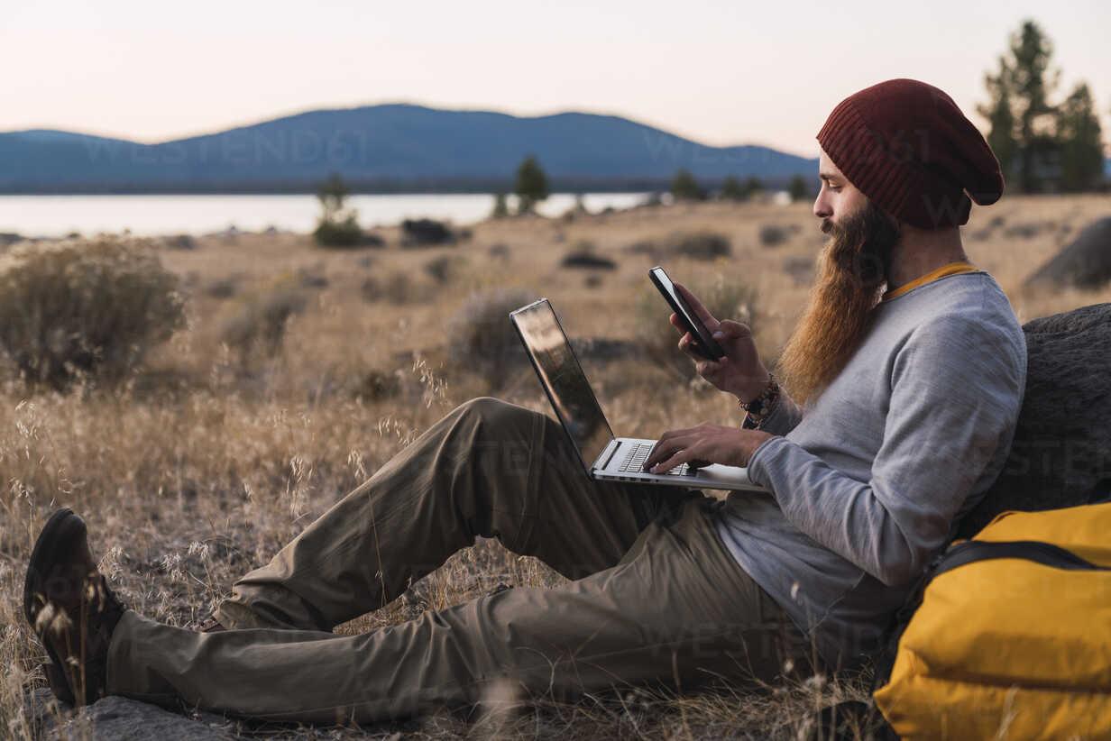 USA, North California, bearded young man using cell phone and laptop near Lassen Volcanic National Park - KKAF02991 - Kike Arnaiz/Westend61
