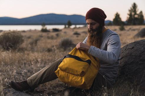 USA, North California, bearded young man having a break on a hiking trip near Lassen Volcanic National Park - KKAF02994