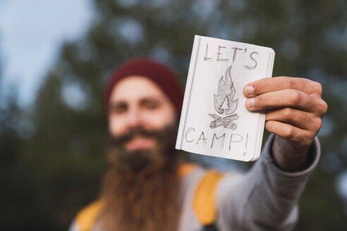 Bearded man in a forest holding 'Let's Camp' sign - KKAF03006