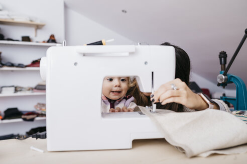 Little daughter watching her mother using sewing machine at home - JRFF02085