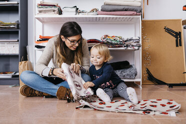 Mother and little daughter sitting on the floor at home checking fabrics - JRFF02094