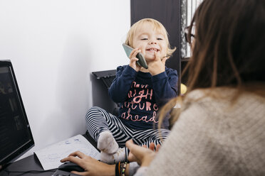 Mother working at home with little daughter sitting on desk holding cell phone - JRFF02109