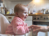 Happy baby girl in sitting in high chair in kitchen - LAF02184