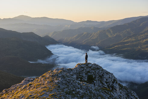 Italy, Umbria, Sibillini National Park, hiker standing on viewpoint at sunrise - LOMF00750