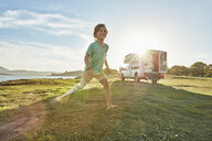 Chile, Talca, Rio Maule, boy running on meadowbeside camper at lake - SSCF00072