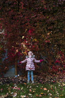 Girl throwing autumn leaves in the air in the garden - PSIF00168