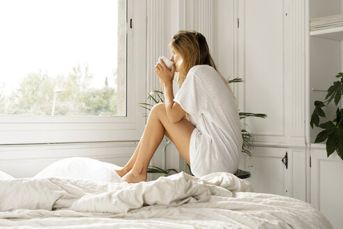 Young woman sitting on bed drinking coffee - ERRF00088