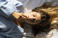 Portrait of beautiful young woman lying in bed with closed eyes - ERRF00094