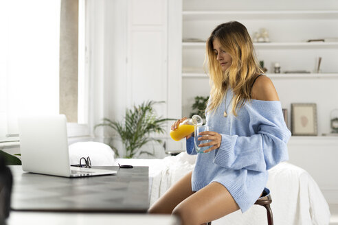 Young woman sitting in bedroom at home pouring orange juice into a glass - ERRF00106