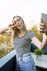 Playful young woman taking a selfie on balcony - VABF01762
