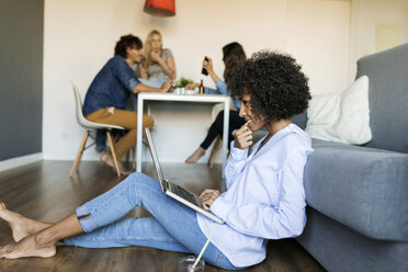 Woman sitting on floor using laptop with friends in background - VABF01768