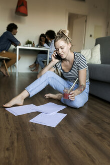 Young woman sitting on floor with cell phone and papers and friends in background - VABF01786