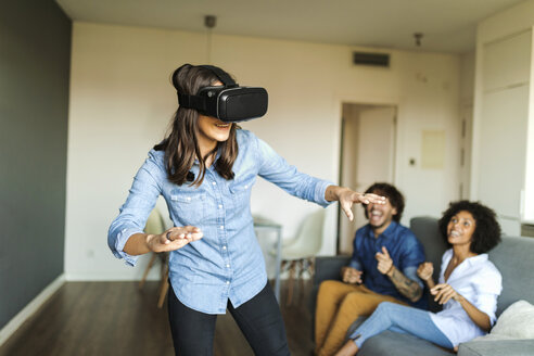 Friends watching woman with VR glasses at home - VABF01789