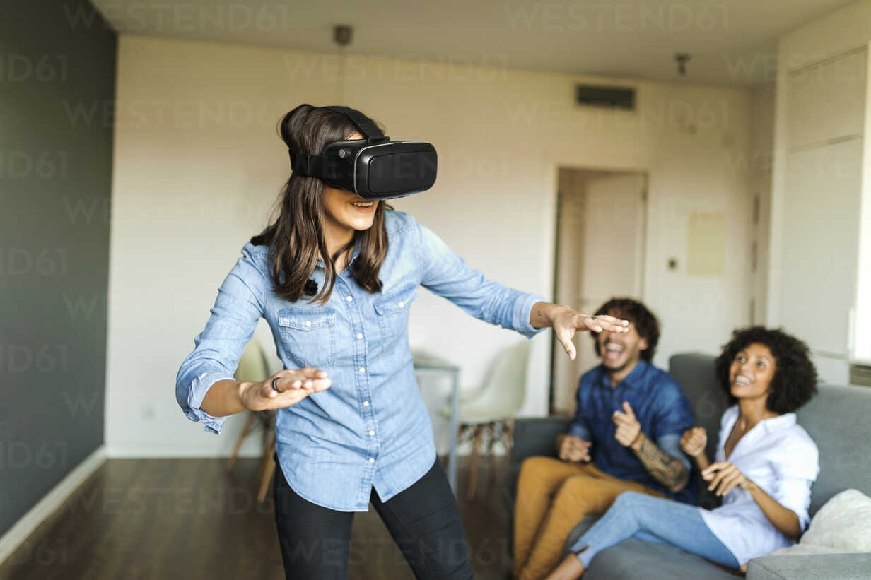 Friends watching woman with VR glasses at home - VABF01789 - Valentina Barreto/Westend61
