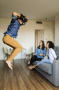 Two women watching man with VR glasses jumping at home - VABF01792