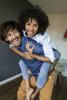 Cheerful man carrying girlfriend piggyback at home - VABF01795