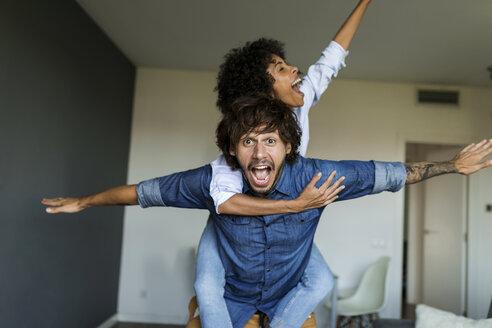 Cheerful man carrying girlfriend piggyback at home - VABF01798