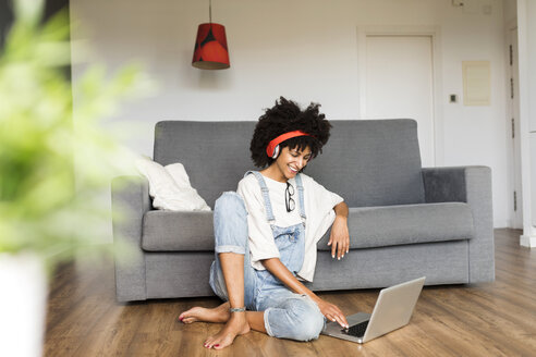 Smiling woman sitting at home with headphones and laptop - VABF01828