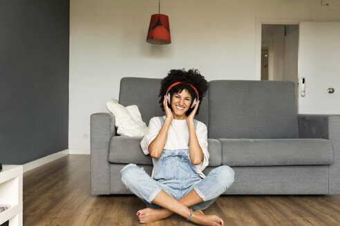 Happy woman sitting at home with headphones - VABF01831