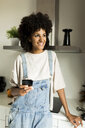 Smiling woman holding cell phone in kitchen at home - VABF01834