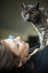 Portrait of grey tabby cat and owner at home - JATF01062