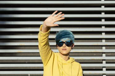 Portrait of young woman with dyed blue hair wearing mirrored sunglasses and yellow hooded jacket - ERRF00111