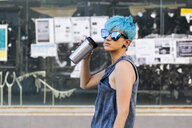 Portrait of young woman with dyed blue hair wearing mirrored sunglasses - ERRF00114