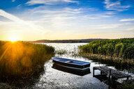 Germany, Mecklenburg-Western Pomerania, Ruegen, Sellin, empty rowing boat near jetty at sunset - FDF00273