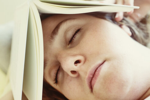 Portrait of young woman sleeping with book on head, close-up - JATF01075