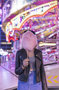 Teenage girl hiding her face behind pink candyfloss at fair - FBAF00168