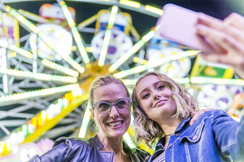 Portrait of mother and daughter taking selfie in front of big wheel at fair - FBAF00174