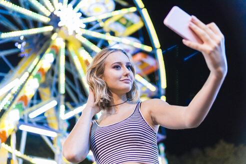 Portrait of teenage girl taking selfie in front of big wheel at fair - FBAF00177