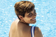 Portrait of winking young woman at swimming pool - ERRF00119