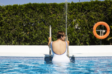 Back view of plump young woman leaving swimming pool - ERRF00122