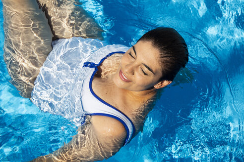 Portrait of plump young woman relaxing in swimming pool - ERRF00128
