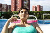 Portrait of young woman relaxing on sun lounger at swimming pool - ERRF00137