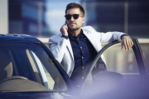 Young businessman standing at his car, talking on the phone - JSRF00074