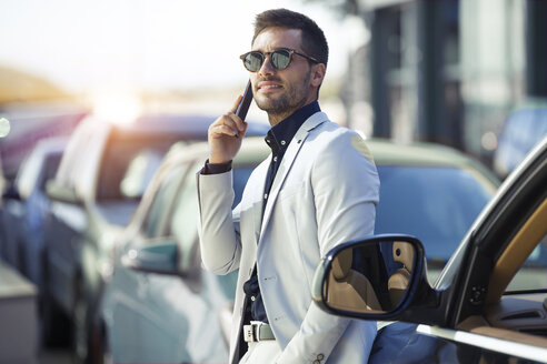 Young businessman commuting in the city, talking on the phone - JSRF00077