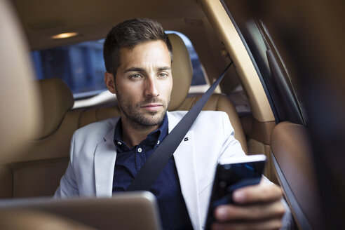 Young businessman sitting in car, using smartphone - JSRF00083