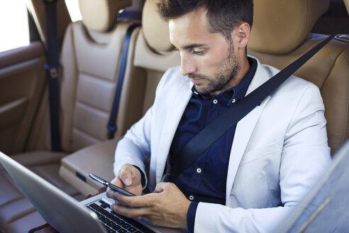 Young businessman working from the backseat of a car - JSRF00086