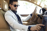 Successful young businessman driving in his car - JSRF00092