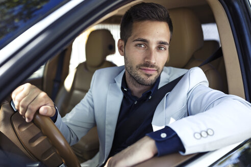 Successful young businessman driving in his car - JSRF00095