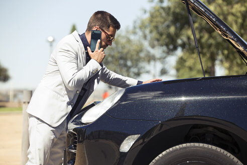 Young businessman having a car breakdown, talking on the phone - JSRF00101