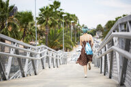 Spain, back view of young woman with blue dyed hair with backpack running on a bridge - ERRF00148