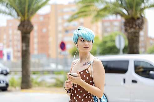 Spain, portrait of young woman with blue dyed hair  listening music with earphones and smartphone - ERRF00151