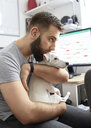 Man cuddling his dog at home office - ZEDF01781